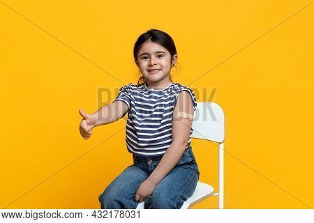 Kids Vaccination. Vaccinated Little Girl Gesturing Thumb Up After Covid-19 Vaccine Injection