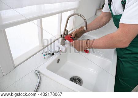 Professional Plumber Fixing Water Tap In Kitchen, Closeup