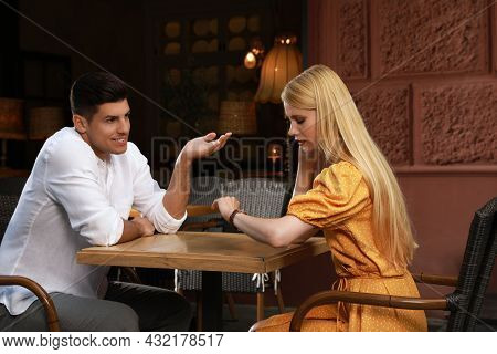 Young Woman Checking Time During Boring Date In Outdoor Cafe