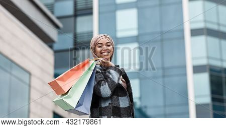 Happy Attractive Muslim Afro American Woman Buyer In Hijab And Coat With Packages With Purchases On