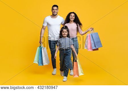 Shopping Day. Cheerful Young Middle-eastern Family Of Three Walking With Shopper Bags