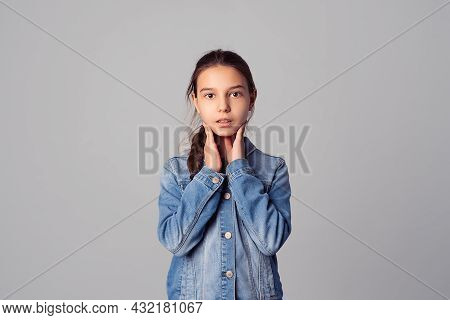 Surprised Preteen Girl Looking At Camera With Wide Opened Eyes And Holds Cheeks By Hand, Isolated On