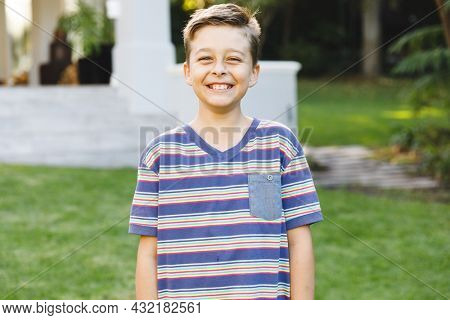 Portrait of smiling caucasian boy outside house looking at camera in garden. spending time at home.