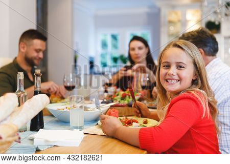 Portrait of caucasian grandfather and parents with daughter sitting at table having dinner. family spending time together at home.