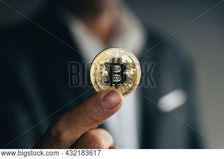 Handsome Investor Businessman In Black Suit Holding A Golden Bitcoin On Dark Background, Trading, Cr