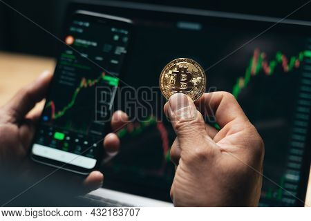 Businessman Holding Golden Bitcoin On Computer Trading Chart Screen Background. Stock, Cryptocurrenc