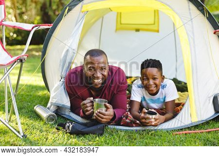 Portrait of african american father with son having fun and lying in tent with drinks in garden. family spending time at home.