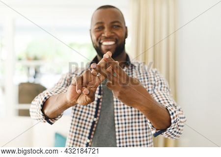 Portrait of african american man smiling and looking at camera in living room talking sign language. communication without words.