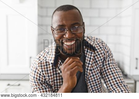 Portrait of happy african american man in kitchen, looking to camera and smiling. spending time at home.
