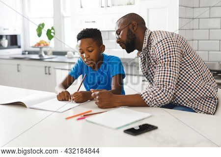 African american father and son in kitchen, doing homework together. family spending time at home, father son relationship.