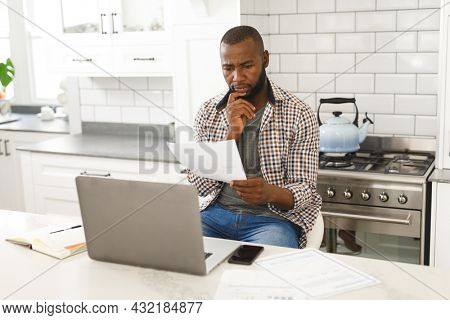 Serious african american man sitting in kitchen working looking at paperwork and using laptop. remote working from home with technology.