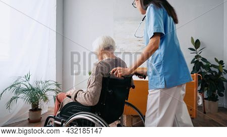 Geriatric Nurse In Eyeglasses Moving Aged Woman In Wheelchair