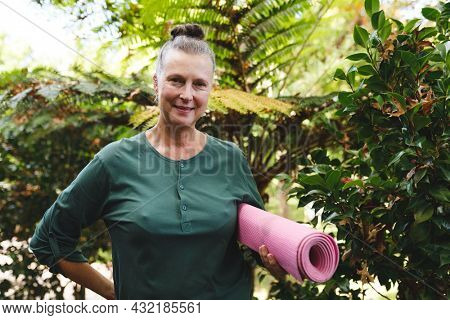 Portrait of happy senior caucasian woman holding yoga mat, looking to camera in sunny garden. healthy retirement lifestyle, spending time at home.