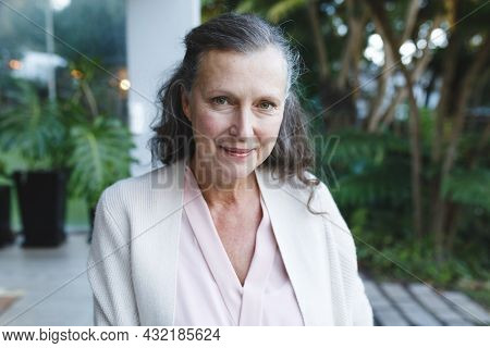 Portrait of happy senior caucasian woman looking to camera and smiling in garden. retirement lifestyle, spending time alone at home.