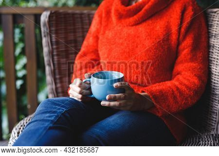 Midsection of senior caucasian woman sitting on chair, holding cup in garden. retirement lifestyle, spending time alone at home.