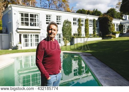 Portrait of happy senior caucasian man looking to camera in sunny garden. luxury retirement lifestyle, spending time at home.