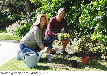 Portrait of happy senior caucasian couple gardening, looking to camera in sunny garden. healthy retirement lifestyle, spending time at home.