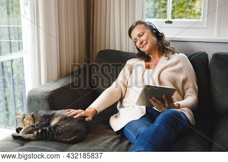 Happy senior caucasian woman in living room sitting on sofa, wearing headphones, using tablet. retirement lifestyle, spending time alone at home with technology.