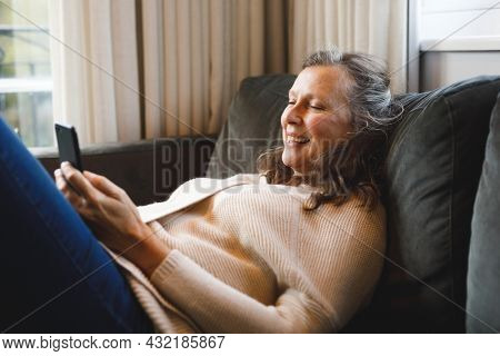 Happy senior caucasian woman in living room sitting on sofa, using smartphone. retirement lifestyle, spending time alone at home with technology.