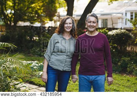 Portrait of happy senior caucasian couple holding hands, looking to camera in garden. retirement lifestyle, spending time at home.