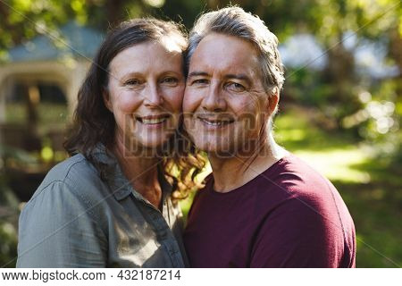 Portrait of happy senior caucasian couple embracing, looking to camera in sunny garden. retirement lifestyle, spending time at home.