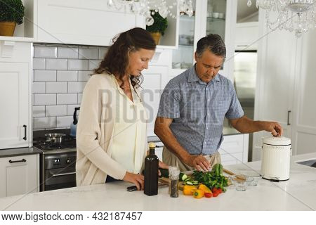 Senior caucasian couple in modern kitchen, cooking together composting organic waste. retirement lifestyle, spending time at home.