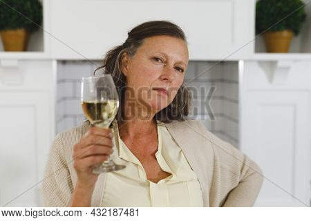 Portrait of senior caucasian woman in modern kitchen, holding glass of wine, looking to camera. retirement lifestyle, spending time at home.