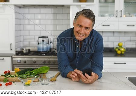 Portrait of senior caucasian man in modern kitchen, using smartphone, looking to camera. retirement lifestyle, spending time at home.