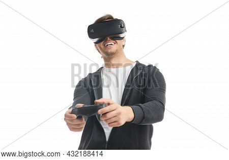 Excited Male Gamer In Vr Headset Using Controller While Playing Videogame During Free Time Against W