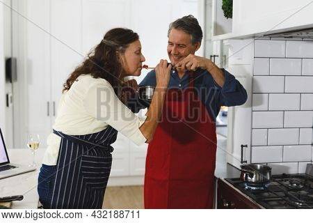 Happy senior caucasian couple in kitchen cooking together, trying food. retirement lifestyle, spending time at home.