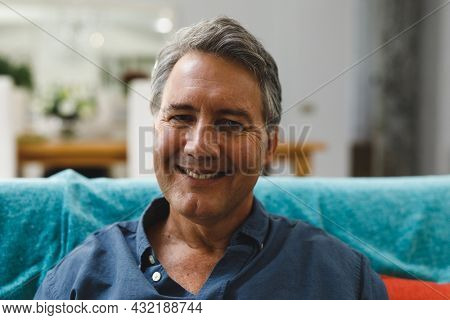 Portrait of happy senior caucasian man in living room sitting on sofa, looking to camera. retirement lifestyle, spending time at home.
