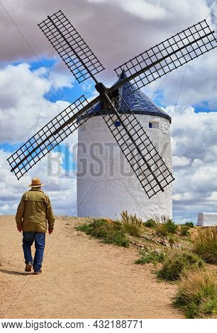 Wind mill at knolls at Consuegra, Toledo region, Castilla La Mancha, Spain. Route of Don Quixote with windmills. Summer landscape with blue sky and clouds.