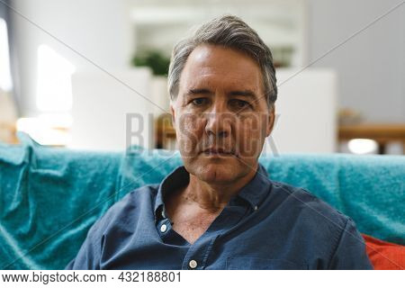 Portrait of sad senior caucasian man in living room sitting on sofa, looking to camera. retirement lifestyle, spending time at home.