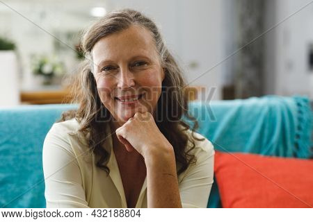 Portrait of happy senior caucasian woman in living room sitting on sofa, looking to camera. retirement lifestyle, spending time at home.
