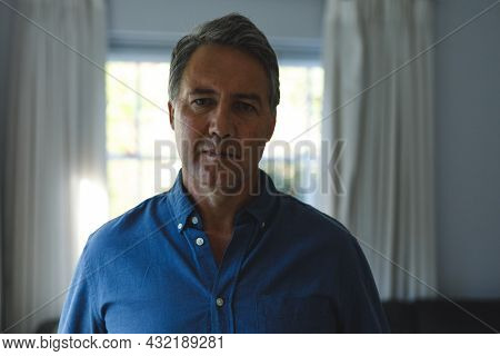 Portrait of thoughtful senior caucasian man standing next to window, looking to camera. retirement lifestyle, spending time at home.