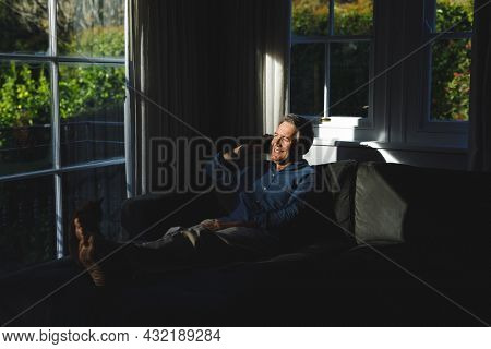 Happy senior caucasian man in living room sitting on sofa, talking on smartphone. retirement lifestyle, spending time at home.