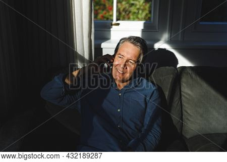 Happy senior caucasian man in living room sitting on sofa, talking on smartphone. retirement lifestyle, spending time at home with technology.