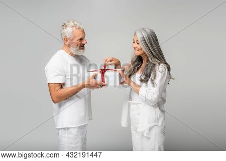Happy Middle Aged Man Holding Wrapped Gift Box Near Curious Asian Wife Isolated On Grey