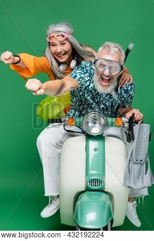Positive And Multiethnic Middle Aged Couple In Goggles With Outstretched Hands Riding Motor Scooter