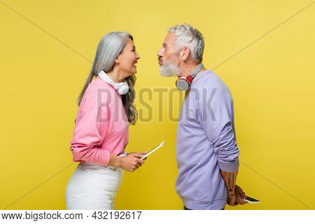 Side View Of Funny Multiethnic And Middle Aged Couple In Wireless Headphones Looking At Each Other A