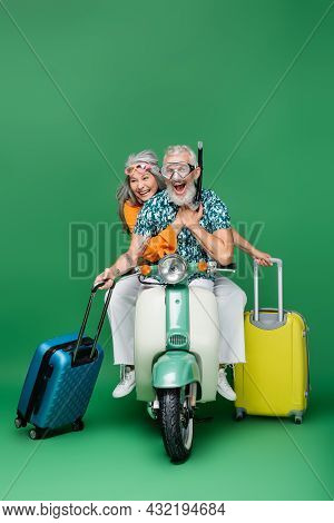 Amazed And Mature Multiethnic Couple In Goggles Holding Luggage While Riding Moped On Green
