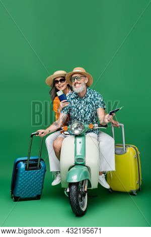 Cheerful Middle Aged And Multiethnic Couple In Sun Hats Holding Passports And Luggage While Riding M