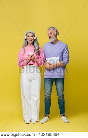 Full Length Of Multiethnic And Smiling Middle Aged Couple In Wireless Headphones Holding Gadgets On