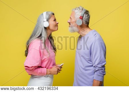 Side View Of Funny Multiethnic And Middle Aged Couple In Wireless Headphones Looking At Each Other I