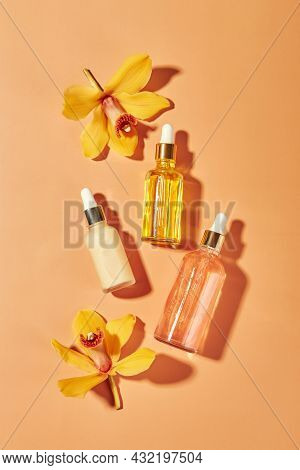 Cosmetic Care Products In Glass Bottles With Orchid Flowers - Serums, Cream, Gel, Oils. Concept For