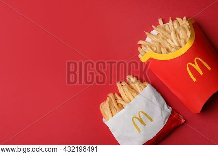 Mykolaiv, Ukraine - August 12, 2021: Small And Big Portions Of Mcdonald's French Fries On Red Backgr
