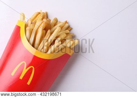 Mykolaiv, Ukraine - August 12, 2021: Big Portion Of Mcdonald's French Fries On White Wooden Table, T