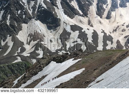 A Group Of Hikers With Backpacks Are Walking Along A Mountain Range Against The Background Of Snowy
