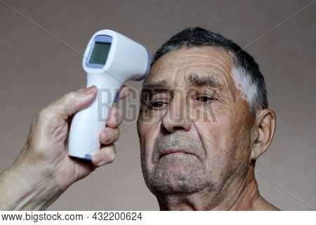 Measuring Body Temperature Of Elderly Man. Digital Infrared Non-contact Thermometer In Hand, Concept