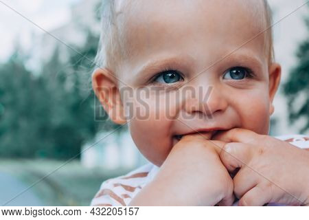 Hapy Little Adorable Caucasian Baby Boy With Amazing Blue Eyes Smiling And Holding Fingers In Mouth.